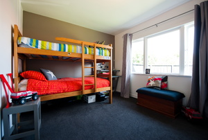 Bedroom with bunk beds, large window, and dark carpet