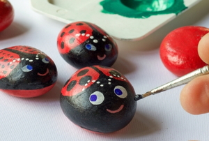 hand painting ladybugs on small rocks
