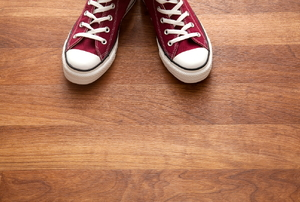 A pair of red sneakers on a wood floor.