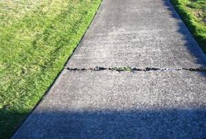 A wide crack in a cement sidewalk.