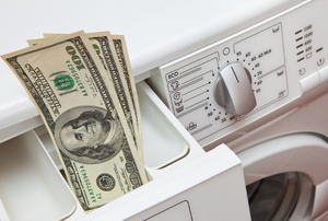A washing machine with cash sitting in one of its drawers.