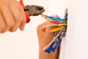 A handyman works on wiring in a home.