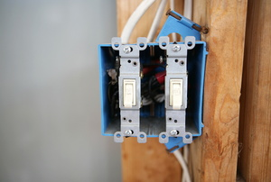 double light switch installed on framing of a wall