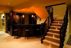 Steps leading down to to a finished basement with a wet bar in the background.