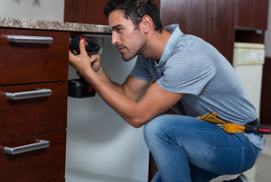 Man installing a base cabinet with drawers.