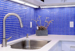kitchen with blue tile backsplash and large stainless steel sink