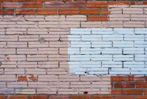 brick wall with red, white, and pink paint