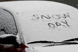 "A car, buried in snow, with ""Snow Day"" written on the window."