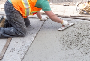 A man works on concrete.