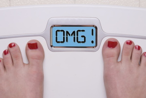 A woman standing on digital weight scale.