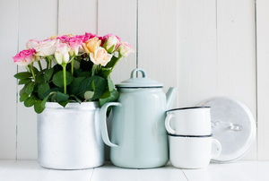 A vintage-looking tea pot surrounded by cups and a vase of roses.