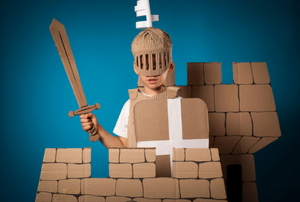 A boy playing in a cardboard castle with a cardboard sword and helmet.