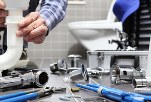 Person in a bathroom with variety of plumbing supplies