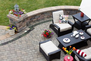 An outdoor seating area and a sitting wall on a paved patio.