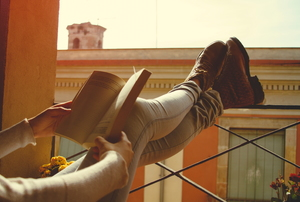 girl reclining on porch while reading book