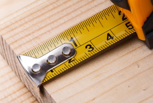 A measuring tape on a plank of wood