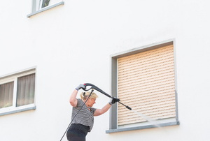 A woman powerwashing her house.