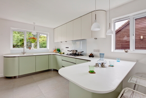 Large kitchen with light green cabinets and white countertops.