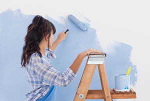 A woman stands on a ladder to roll light blue paint onto a white wall.
