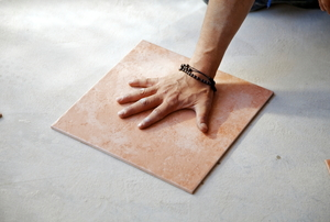 Hand on a square of porcelain tile.