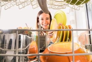 smiling woman loading or unloading dishwasher