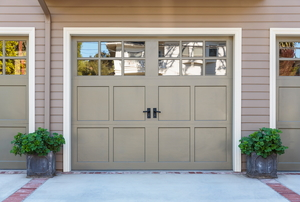 A tan garage door with windows.