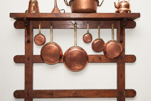 Copper pots and pans hanging from a wooden rack.