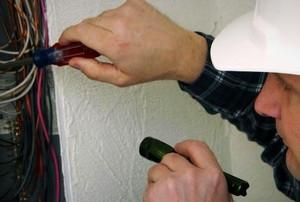 a man checks wiring in a breaker box