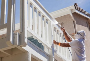 person spray painting balcony railing white