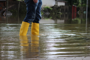 A woman wears yellow rain boots in a flood.