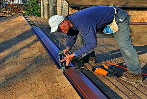 A man caulking a ridge vent.