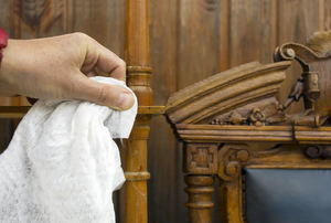 Wiping an antique chair with a white cloth