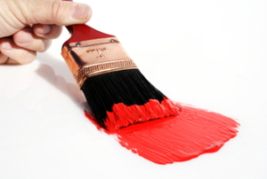 A paint brush is used to paint a streak of red.