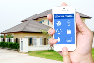 A hand holding a smart phone in front of a house.