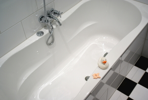 bathtub with rubber ducky sitting on the edge