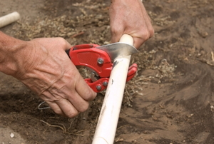 Close up of a man's hands cutting a piece of PVC irrigation pipe.