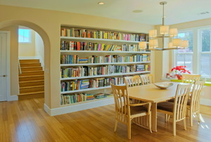 A dining room with built-in bookshelves.
