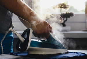 hand ironing fabric with steaming iron
