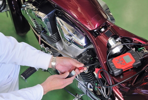 person working on a burgundy-colored motorcycle