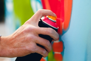 a hand spray painting a white surface with colors