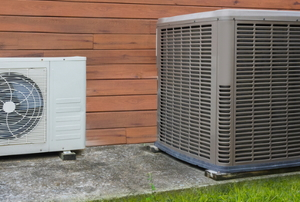 A heat pump mounted beside an air conditioner unit.