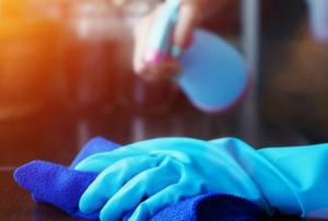 gloved hands cleaning with a spray bottle and cloth