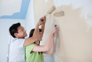 A young couple smiling and painting their new place.