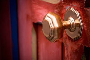 A brass doorknob on a red door.