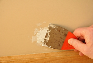 A closeup of a putty knife spreading spackle on a wall.