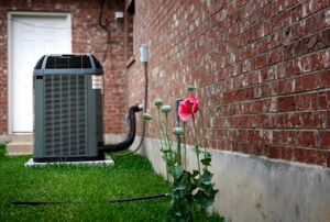 A central air conditioning unit connected to a home from the outside.