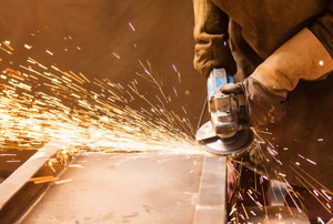 sparks fly as a person with gloves uses an angle grinder