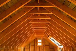 Looking down a long, empty attic toward a single window.