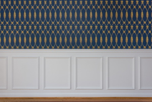 Wall with wallpaper on upper and wainscoting on lower.