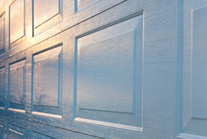 A new aluminum garage door with the sunrise reflecting off of the white surface.